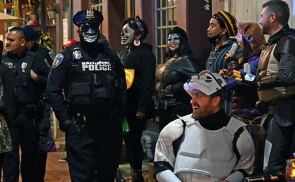 A Baltimore City Police officer walks past costumed people listening to a band performing outside the Waterfront Hotel on Thames Street in Fells Point last Halloween. October 31, 2020. (Kim Hairston/Baltimore Sun).