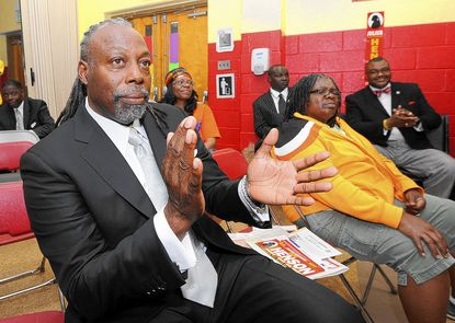 Julius Henson, foreground left, listens as other politicians running in the 45th district campaign speak to the audience at a Political Forum at Fort Worthington Elementary School Recreation Center on Hoffman St. Henson, who is running for a Maryland senate seat, also spoke.