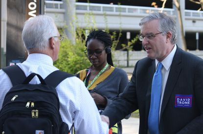 David Trone, right, owner of wine superstore chain Total Wine and More, greets commuters at the Shady Grove Metro station, in Derwood, Md. Trone, who is running in the Democratic primary for Maryland's 8th Congressional District, has put more than $12 million of his own money into his campaign.