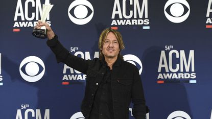 Keith Urban poses in the press room with the award for entertainer of the year at the 54th annual Academy of Country Music Awards at the MGM Grand Garden Arena on Sunday, April 7, 2019, in Las Vegas.
