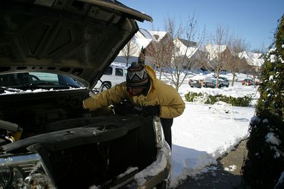 Ricardo Matiz checks the fluids to his car following a snow fall, Jan. 3.