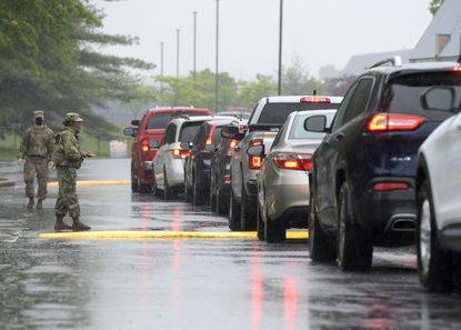 Maryland National Guard members direct traffic at the COVID-19 testing center housed in the Vehicle Emission Inspection Program station in Glen Burnie.
