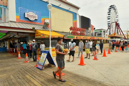 """President Donald Trump's freezing of visas for temporary foreign workers will """"further weaken"""" the national economy and bar workers who normally support tourism and other important Maryland industries, U.S. Sen. Chris Van Hollen said Tuesday. A May 17, 2020, photo, shows the boardwalk at Ocean City, which is home to seasonal workers each summer."""