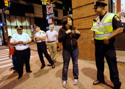 Baltimore Mayor Stephanie Rawlings-Blake, second from right, shows her Orioles sweatshirt off to Baltimore Police officer Fabien Laronde, right while walking around downtown Baltimore Friday, May 19, 2012.