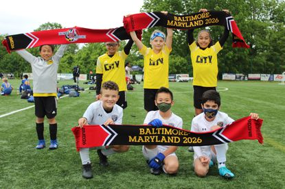 Kids who took part in a soccer tournament last month hold up scarves advocating bringing the World Cup to the Baltimore region in 2026.