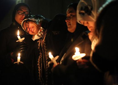 Nida Allam, a senior at North Carolina State University, rests her head on Asheen Allam during a candlelight vigil for in Chapel Hill, N.C.