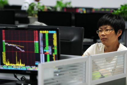 An investor looks at stock prices at a securities company in China.