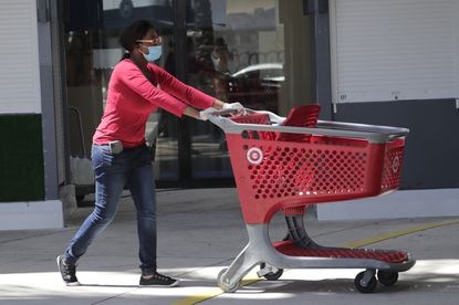 An employee of Target wears a protective face mask and gloves May 7, 2020, as she works outside a Target store in Miami. On June 17, the retailer said it would permanently raise its starting wages to $15 an hour in July.
