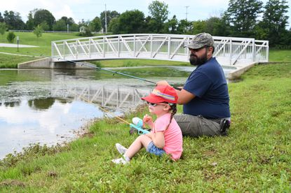 Brian Mahuta of Westminster and his 2-year-old daughter Bridget practice their fishing technique at the Westminster Community Pond on Monday, August 17.