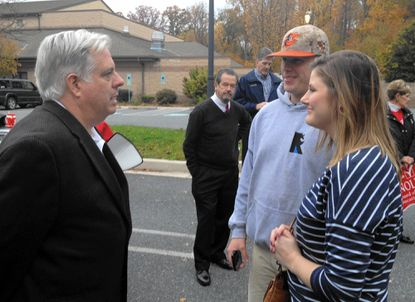 Larry Hogan, left, the Republican gubernatorial candidate, talks to Edgewood residents Amy Finch and Daniel Wehr outside the McFaul Activities Center in Bel Air Thursday.