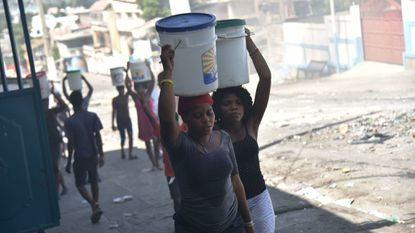 Women carry buckets of water on a barricaded street in central Port-au-Prince on Monday after two days of deadly looting and arson triggered by a quickly aborted government attempt to raise fuel prices.