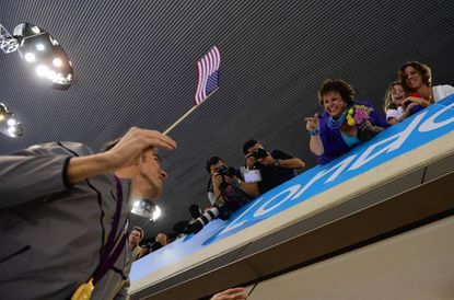 Michael Phelps waves a U.S. flag in view of his mother Debbie (top center) and sister Whitney (right) after he won gold in the men's 4x100 medley relay on Aug. 4.