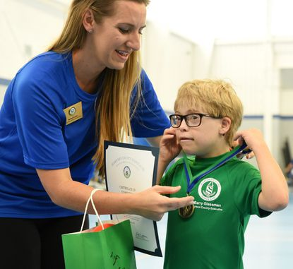 Rachel Harbin, Coordinator Harford County Office of Disabilities, left presents camper Ian Feiler of Abingdon with his medal and other fun items on the final day of the 2018 Harford County iCan Bike Camp at the Churchville Rec Center.