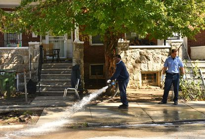 Firefighters clean the sidewalk in the 4900 block of Queensberry Avenue near W. Garrison Avenue, where one man was shot, shortly before noon on Monday morning. The victim was taken to Sinai Hospital.