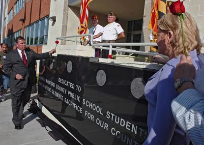 A memorial to students who died serving their country in the military was dedicated by Harford County Public Schools in front of the school system's Bel Air Headquarters in May 2007. Participating were Michael Adle, left, and Pamela Watts, right, the parents of Marine Lance Cpl. Patrick Adle, a Fallston High School graduate who was killed while serving in Iraq in 2004. Earlier, school officials had declined a request to name the Fallston High football field in honor of Lance Cpl. Adle.