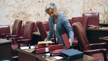 Renee Smoot, chief page, removes bill binders from the desks of senators on the eve of the start of the General Assembly session.