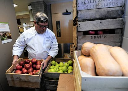 Bob Lavoie, campus executive chef at the Johns Hopkins University, moves a crate of apples in Fresh Food Cafe. The apples and butternut squash are from Licking Creek Bend Farm in Pennsylvania. The dining hall in the freshman quad gets much of the produce, meat and seafood from local sources.