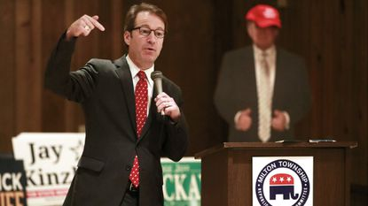 Republican U.S. Rep. Peter Roskam speaks in front of a cardboard cutout of President Donald Trump at the DuPage County Milton Township committeeman's meeting at the Wheaton Bowl in Wheaton, Ill., on Oct. 10, 2018.