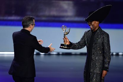 """John Oliver, left, accepts from Billy Porter the """"Outstanding Variety Talk Series"""" award for """"Last Week Tonight with John Oliver"""" onstage during the 71st Emmy Awards at the Microsoft Theatre in Los Angeles on Sept. 22, 2019."""