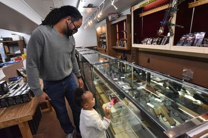 Devrin Bowling of Owings Mills, with his two-year old daughter, Emory, looks at the display of pistols at Maryland Elite Firearms. Dan Hartman, owner of the gun shop, reports that gun sales have been up since last February-March, coinciding with COVID, Black Lives Matter protests, and the upcoming election. Oct. 27, 2020.