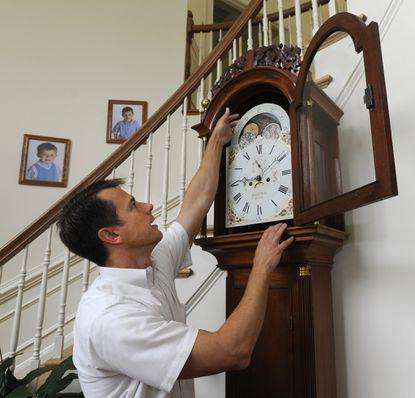 John Danko examines a War of 1812-era grandfather clock he built.