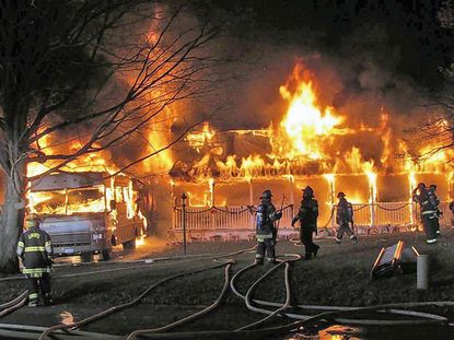 Fire engulfs a home and camper in the 2400 block of Bluefield Circle in Joppa Monday evening. Firefighters from eight volunteer and paid fire companies responded.