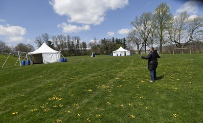 Director of Citizen Services Celene Steckel shows the outside area available for distanced tent camping on April 15 at East Middle School, which has been converted for use as a medical respite for homeless individuals.