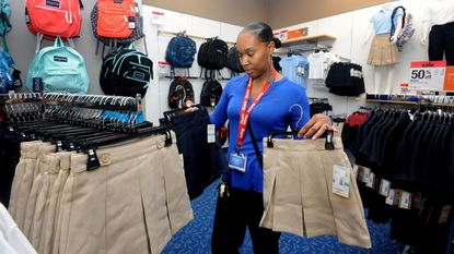 White Marsh MD -- Tierra Taylor-Ba, the general manager for Sears at White Marsh, holds up skirts to girls' uniforms sold at the store in this file photo from August 2016.