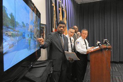 Left, using a monitor, Baltimore Police spokesman T.J. Smith, points out the area where Alex Michael Brizzi entered Fox 45 yesterday. On right is Commissioner Kevin Davis. Brizzi, of Elkridge, walked into the vestibule of the television station dressed in a hedgehog costume and carrying a suspected explosive device. He was shot by police outside the building. The most serious charges are second-degree arson and first-degree malicious burning which are felonies.
