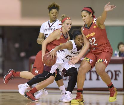 UMES guard Ra'Jean Martin dribbles into the defense of Maryland center Brionna Jones (Aberdeen), right, and guard Kristen Confroy.