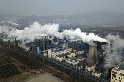 In this Nov. 28, 2019 file photo, smoke and steam rise from a coal processing plant that produces carbon black, an ingredient in steel manufacturing, in Hejin in central China's Shanxi Province. (AP Photo/Sam McNeil, File)