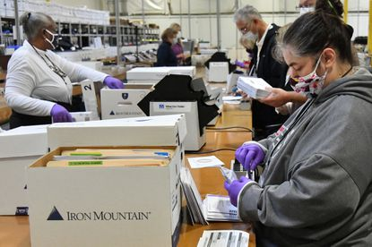 Jerri Waldroff, right, and other canvassers begin counting early ballots received from ballot drop boxes and by mail at the Anne Arundel County Board of Elections on Monday. (CQ on name) Oct. 5, 2020.