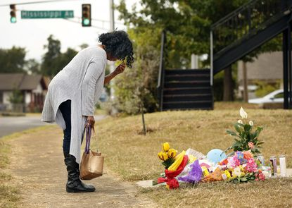 Lynda Menefee, of Fort Worth, makes the sign of the cross after leaving flowers on the front sidewalk of Atatiana Jefferson's home in Fort Worth, Texas. Jefferson, a black woman, was shot by a white police officer early Saturday, Oct. 12.