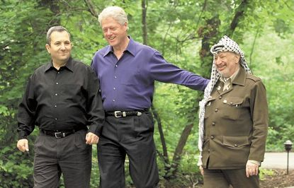 President Clinton, center, accompanied by Israeli Prime Minister Ehud Barak, left, and Palestinian leader Yasser Arafat, right, walk on the grounds of Camp David July 11, 2000, during a Mideast summit.