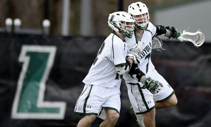 Loyola midfielder Jeff Chase (12) and attackman Pat Spencer (7) celebrate Chase's goal during Loyola's win against Johns Hopkins.