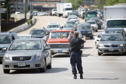 A Baltimore Police officer directs traffic at the exit of the Jones Falls Expressway at Fayette and South President streets.