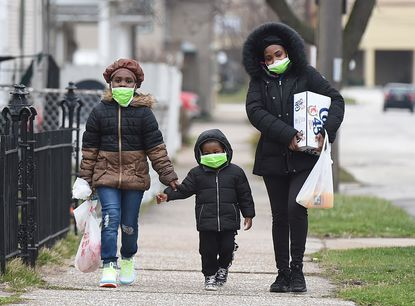 Marla Beason of Erie, and her children Samori, 8, left, and Durrell, 4, walk March 20, 2020, to their home in the 300 block of West 17th Street in Erie, Penn. after shopping at a nearby store.