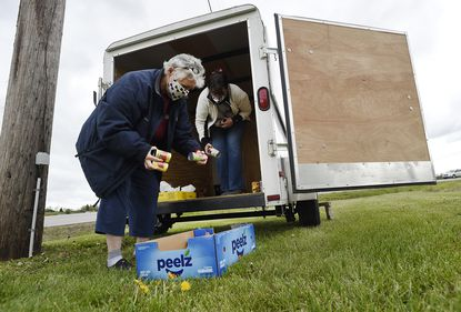 Donna Babylon, left, and Tammy Ray load donations onto their trailer along Wakefield Valley Road Monday, April 27, 2020. Babylon Vault Company has organized a community food drive, placing a trailer at the corner of Wakefield Valley Road and Route 31 to collect non perishable food items for the community.