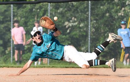 Patterson Mill infielder Aiden Laurentius tries to make the diving catch on the bouncing grounder during a Class 1A state quarterfinal game against Catoctin at Patterson Mill on Monday. The Huskies lost, 3-1.
