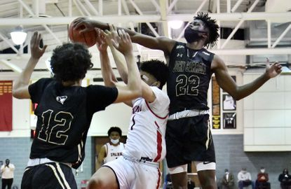 Archbishop Spalding #1 C.J. Scott gets squeezed by the defense of John Carroll's # 12 Tyson Commander and #22 Jeannot Basima. John Carroll beat Archbishop Spalding, 69-66, in a BCL semifinal game, and will face St. Frances in the championship game.
