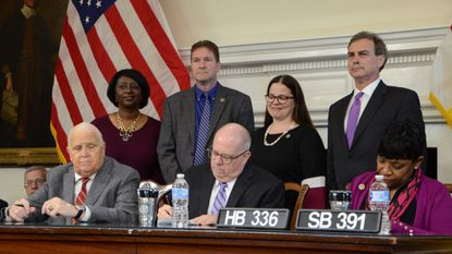 Gov. Larry Hogan signed a bill into law Tuesday that creates a fund to give loans to federal employees required to work without pay during government shutdowns. He was joined at the table by Senate President Mike Miller, left, and House Speaker Pro-tem Adrienne Jones, right.