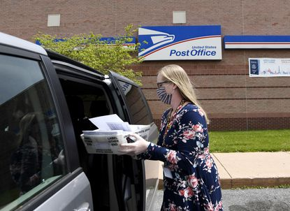 Carroll County election director Katherine Berry carries mailed-in ballots she picked up at the Post Office in Westminster Tuesday, May 19, 2020.