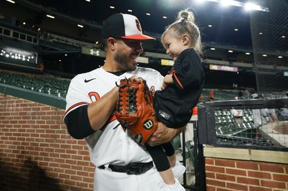 Orioles relief pitcher Manny Barreda talks to his daughter, Sofia, 2, after he recorded the win during his professional debut against the Kansas City Royals on Wednesday night.