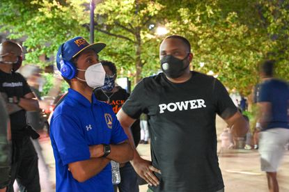 Brandon Scott, left, hears from activist Kwame Rose as protesters face off with police at Baltimore City Hall in response to the police custody death of George Floyd in Minneapolis.