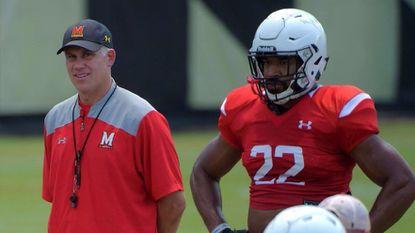 Maryland Isaiah Davis stands beside coach D.J. Durkin during team football practice drills.
