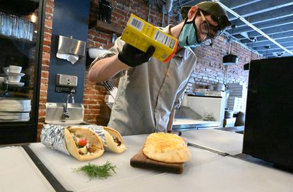 Brendin McCuen, head chef at Jaxon Edwin Social House, sprinkles Old Bay seasoning on a Crab Dip Flat Bread as he prepares a food order on Friday, May 15, 2020. Jaxon Edwin was renovated by Gordon Ramsay during his visit to Ellicott City. (Brian Krista/Baltimore Sun Media).