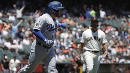 Dodgers first baseman Max Muncy gestures after hitting a home run against San Francisco Giants pitcher Madison Bumgarner, right, during the first inning of the Dodgers' 1-0 victory Sunday.