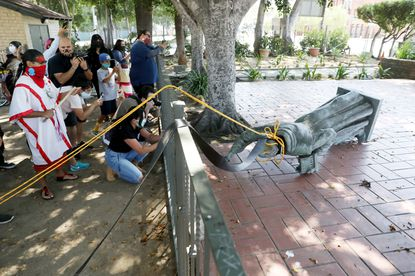 Activists topple the statue of Father Junipero Serra at Father Serra Park in El Pueblo de Los Angeles on June 20, 2020, in downtown Los Angeles. Junipero Serra (1713-1784) is a Roman Catholic Spanish priest who founded the first nine of 21 Spanish missions, from San Diego to San Francisco, in what was then Spain's Alta California. (Gary Coronado/Los Angeles Times).