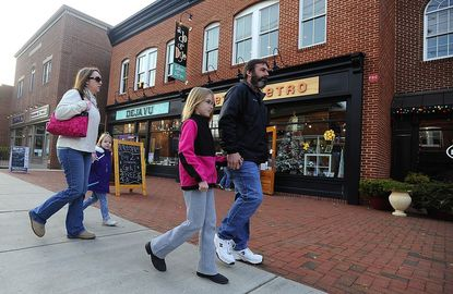 Jason and Melanie Martindale walk with their daughters Megan, 8, and Jessie, 5, along Main Street in downtown Mount Airy Saturday.