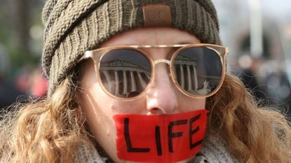 The U.S. Supreme Court is reflected in the glasses of pro-life protester Kim Lockett who is wearing red tape that reads LIFE during the Right To Life March on January 18, 2019 in Washington, DC.